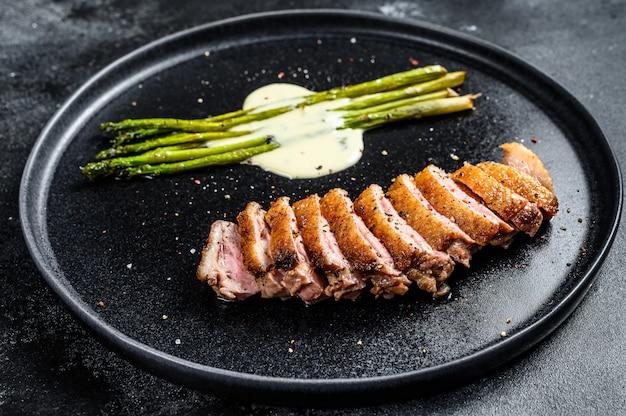 Gegrilde eendenfilet steaks met asperges. zwarte achtergrond.