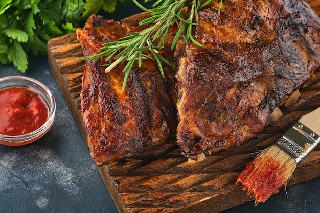 Gegrilde en gerookte varkensribbetjes met barbecuesaus op een oude vintage houten snijplank. lekkere snack tot bier. close-up beeld.