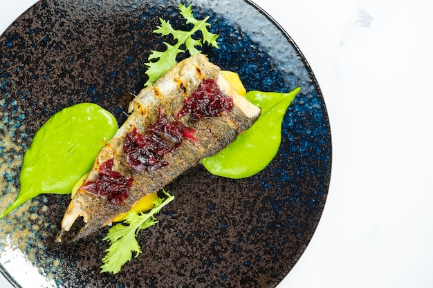 Gegrilde forel met gekarameliseerde bieten en groene puree op een zwarte plaat op een marmeren tafel. zeevruchten. maaltijd met vis.