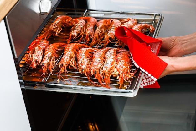 Gegrilde garnalen en gebakken garnalen thuis keuken. vrouw met een garnalenbarbecue op een roestvrijstalen dienblad en koken in een elektrische oven om een nachtfeest te vieren. zeevruchten.
