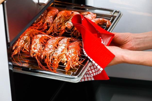 Gegrilde garnalen in de oven van de thuiskeuken en met de hand de roestvrijstalen plaat eruit trekken met een keukendoek