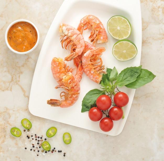 Gegrilde garnalen met basilicum en cherry tomaten op een witte plaat