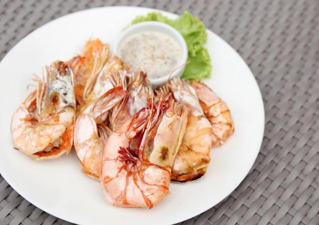 Gegrilde garnalen met zeevruchtensaus op een witbord