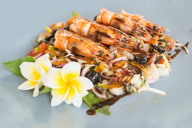 Gegrilde garnalen of gamba's met gebakken groenten op achtergrond versierd met frangipanibloem