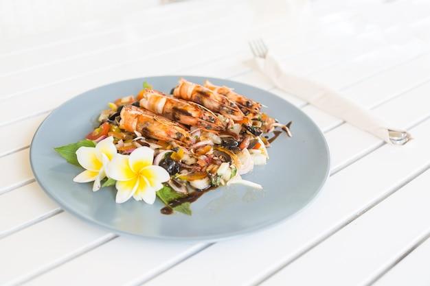 Gegrilde garnalen of gamba's met gebakken groenten op blauw bord versierd met frangipanibloem