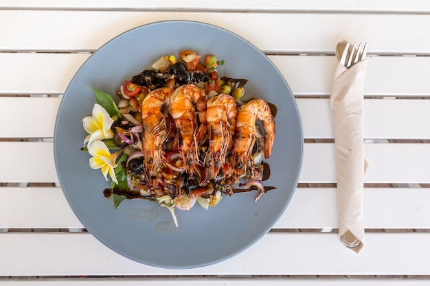 Gegrilde garnalen of gamba's met gebakken groenten op het lichtblauwe bord met frangipanibloem