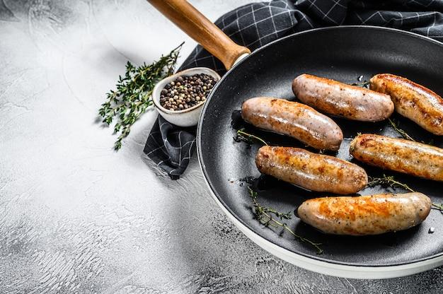 Gegrilde geassorteerde varkens-, rundvlees- en kippenworstjes met kruiden in een pan. grijze achtergrond. bovenaanzicht. kopieer ruimte.