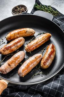 Gegrilde geassorteerde varkens-, rundvlees- en kippenworstjes met kruiden in een pan. grijze achtergrond. bovenaanzicht.