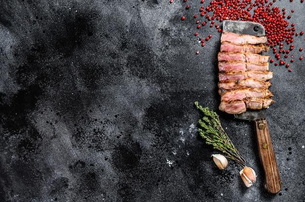 Gegrilde gesneden varkenslapje vlees op een hakmes. biologisch vlees. zwarte achtergrond. bovenaanzicht. kopieer ruimte.