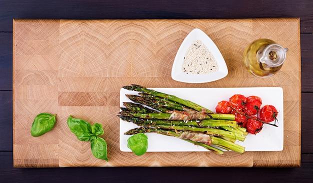 Gegrilde groene asperges omwikkeld met spek op houten tafel. bovenaanzicht