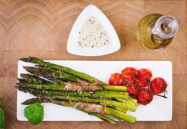 Gegrilde groene asperges omwikkeld met spek op houten tafel