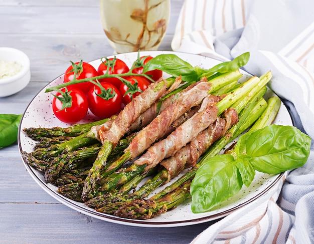 Gegrilde groene asperges omwikkeld met spek op houten tafel.