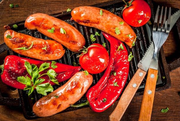 Gegrilde groenten en worstjes op een gegrilde bakplaat met specerijen en kruiden.