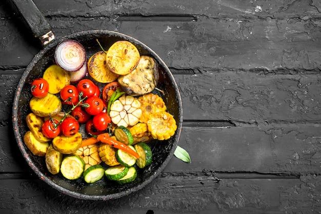 Gegrilde groenten in een pan met kruiden en specerijen op donkere rustieke tafel.
