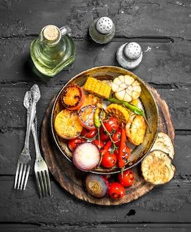 Gegrilde groenten in een pan met kruiden op donkere rustieke tafel.