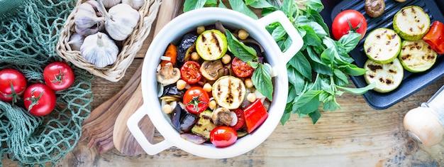 Gegrilde groenten in een witte keramische pan met ingrediënten op een rustieke ondergrond