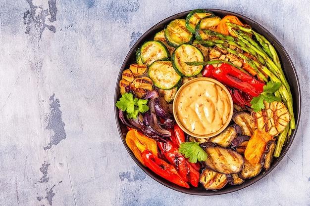 Gegrilde groenten op een bord met saus