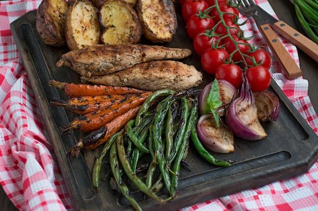 Gegrilde groenten op een snijplank op een donkere houten achtergrond. donkere houten achtergrond.