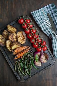 Gegrilde groenten op een snijplank op een donkere houten tafel. donkere houten tafel.