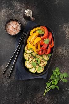 Gegrilde groenten stukjes courgette, rode en gele paprika en een boeket koriander op plaat, salade op bbq grillrek boven houtskool. barbecue concept.