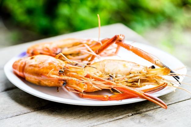 Gegrilde grote garnalen zeevruchten koken op de houten tafel, zeevruchten gegrilde barbecue in vakantie