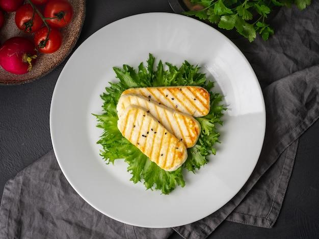 Gegrilde halloumi, gebakken kaas met sla salade. uitgebalanceerd dieet, witte plaat op donker