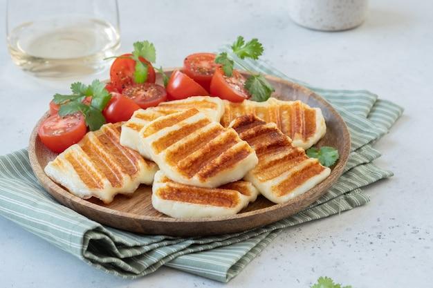 Gegrilde halloumi-kaas en verse tomatensalade.