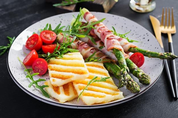 Gegrilde halloumi-kaassalade met tomaten en asperges in reepjes spek op plaat op donkere achtergrond. gezond eten.