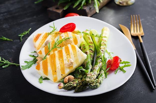Gegrilde halloumi-kaassalade met tomaten en asperges op plaat op donkere achtergrond. gezond vegetarisch eten.