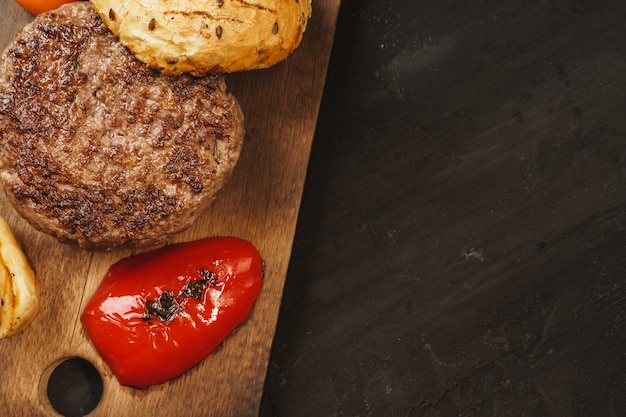 Gegrilde hamburgerkotelet met een broodje op een houten bord, bovenaanzicht