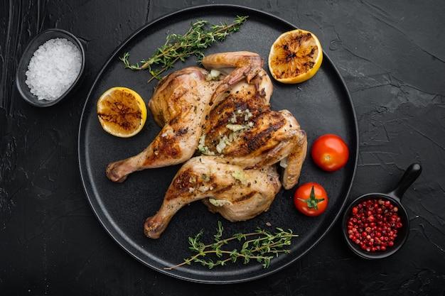 Gegrilde hele kip, met chimichurri-saus, op zwarte achtergrond, bovenaanzicht