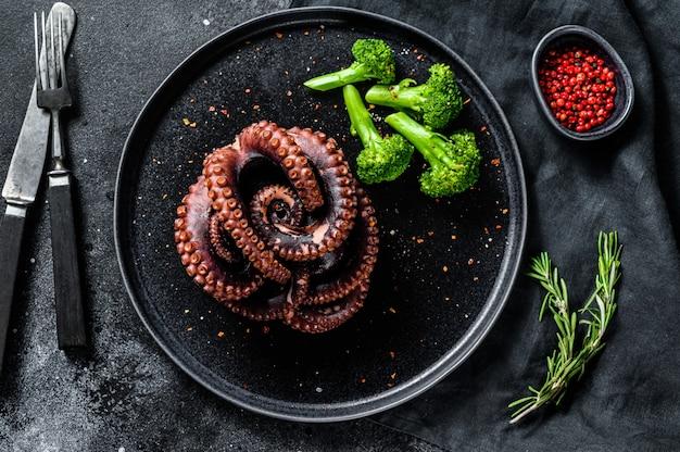Gegrilde hele octopus met broccoli op een bord. bovenaanzicht