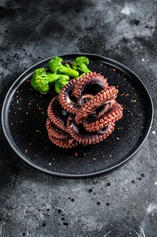 Gegrilde hele octopus met broccoli op een plaat. zwart oppervlak. bovenaanzicht