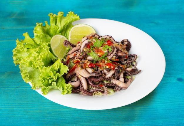 Gegrilde inktvis gegarneerd met zeevruchten saus op een witte plaat met sla en citroen decoratie geplaatst op een blauwe houten tafel.