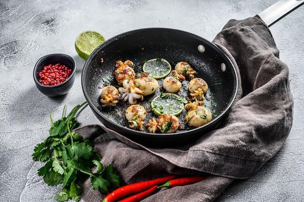 Gegrilde inktvis met limoen en kruiden in een pan. grijze achtergrond. bovenaanzicht