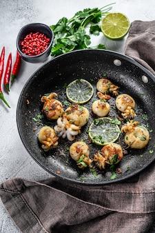 Gegrilde inktvis met limoen en kruiden in een pan