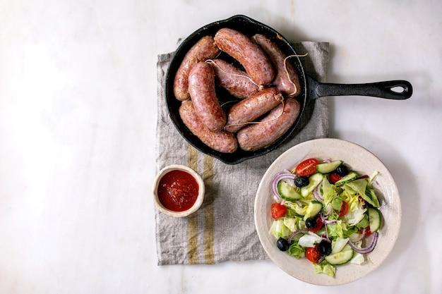 Gegrilde italiaanse worstsalsiccia in gietijzeren pan geserveerd met tomatensaus en plaat van verse groentesalade. plat leggen, kopie ruimte