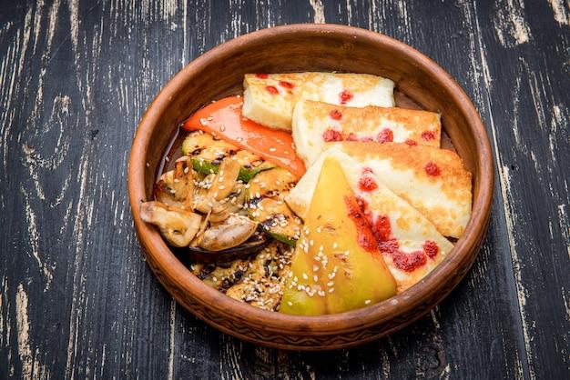 Gegrilde kaas met gegrilde groenten in een kleiplaat