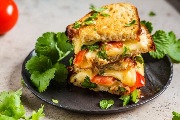 Gegrilde kaassandwich met tomaat en greens, donkere achtergrond.