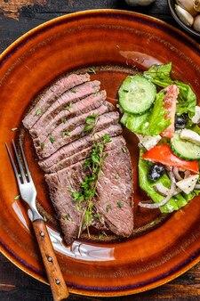 Gegrilde kalfskotelet steak op een bord met salade. donkere houten achtergrond. bovenaanzicht.