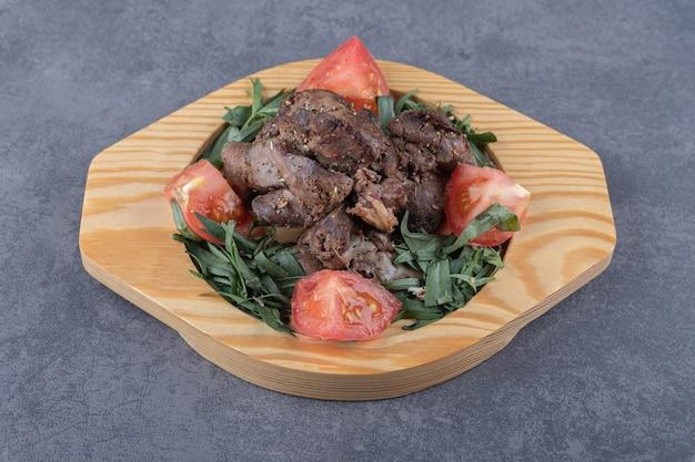 Gegrilde kebab en tomaat plakjes op houten plaat.