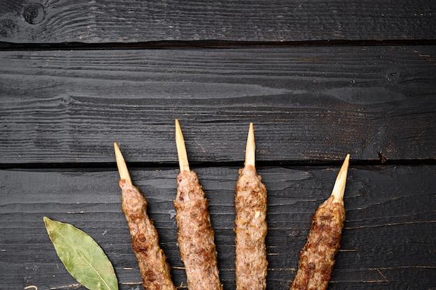 Gegrilde kebab set, op zwarte houten tafel achtergrond, bovenaanzicht plat lag, met kopieerruimte voor tekst
