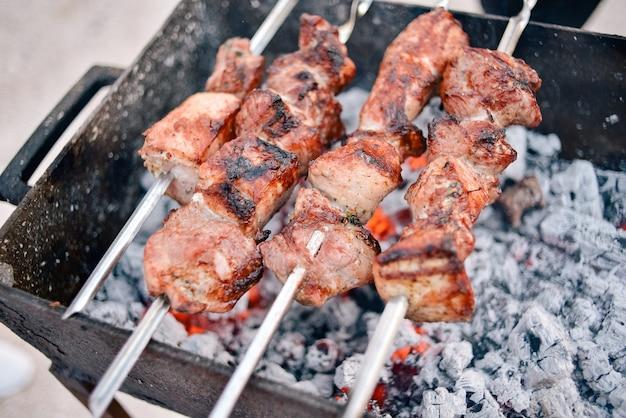 Gegrilde kebab. varkensspiesjes worden gekookt op houtskool. picknick op straat. kebab, barbecue