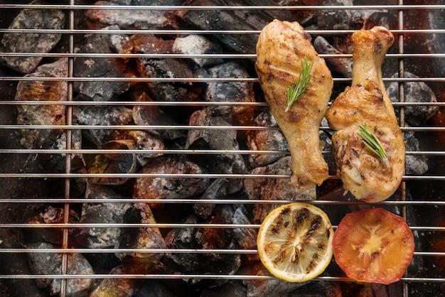 Gegrilde kip drumstick boven vlammen op een barbecue