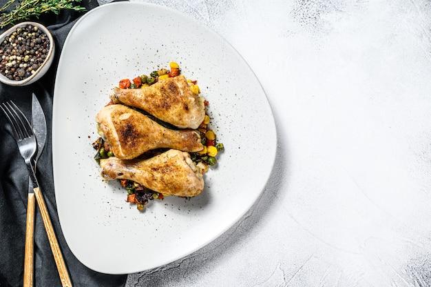 Gegrilde kip drumsticks met groenten op een witte plaat. witte achtergrond. bovenaanzicht. kopieer ruimte