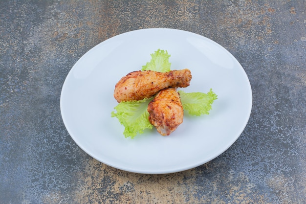 Gegrilde kip drumsticks op plaat met sla. hoge kwaliteit foto
