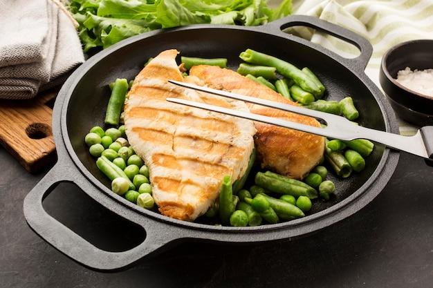 Gegrilde kip en erwten onder hoge hoek in de pan