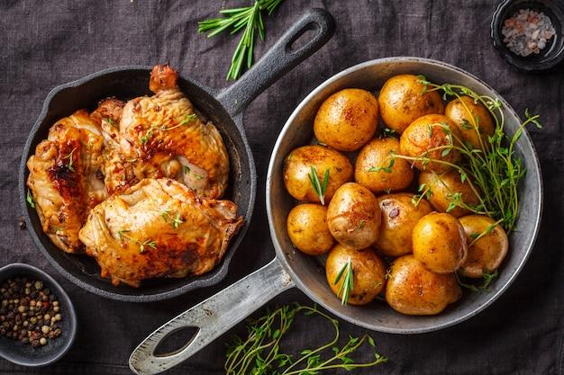Gegrilde kip en gebakken aardappelen in een gietijzeren koekepan.