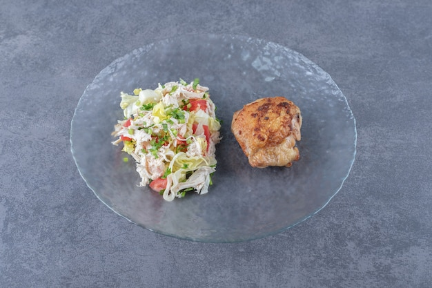 Gegrilde kip en groentesalade op glasplaat.