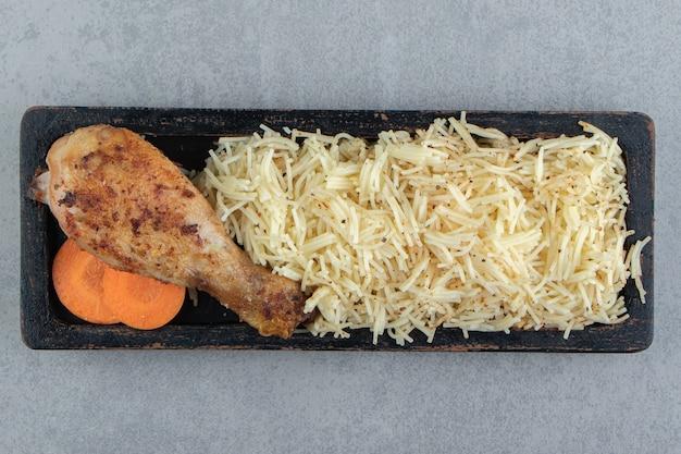 Gegrilde kip kippenpoot en pasta op zwarte plaat. Gratis Foto